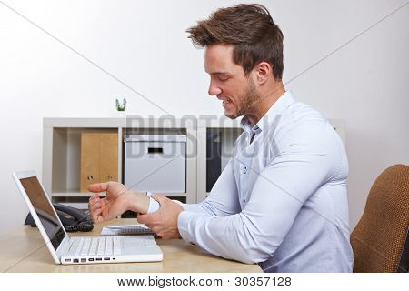 Business man in office with RSI syndrome holding his aching hand