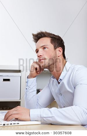 University student at laptop with writer's block whilw working on final thesis