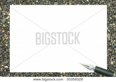 white paper and a pen on a pile of rocks