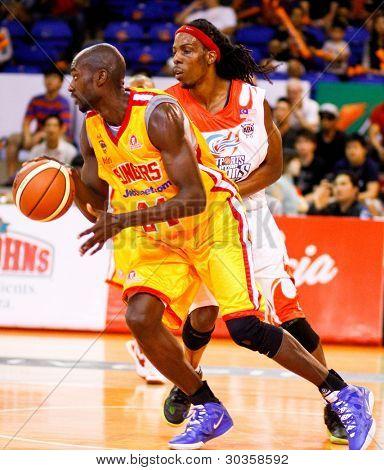 KUALA LUMPUR - FEBRUARY 19: Singapore Slingers' Louis Graham (yellow) dribbles past Tiras Wade at the ASEAN Basketball League match on February 19, 2012 in Kuala Lumpur, Malaysia. Dragons won 86-71.