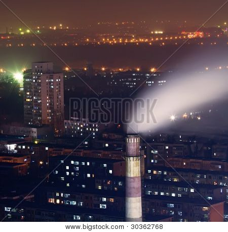 Night Scene Of Chimney With Smoke In Residents Area In Heavy Fog
