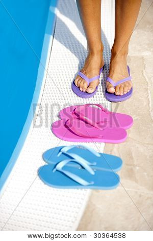 Female legs with colorful slippers by pool