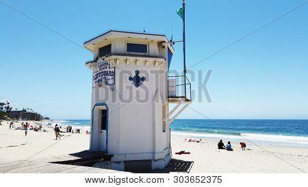 LAGUNA BEACH, CALIFORNIA - MAY 28, 2019: Lifeguard Tower and sunbathers on Main Beach in the popular Southern California beach town.
