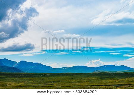 Spectacular View Of Giant Mountains With Snow. Huge Cloud Above Mountain. Big Rocky Cliff Above Abys