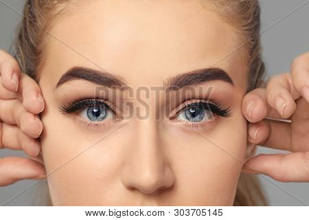 Young woman with beautiful eyebrows on grey background, closeup
