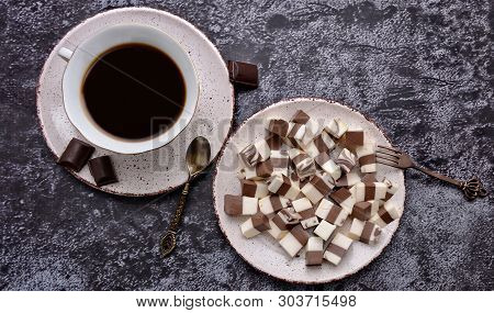 Cup Of Coffee And Delicious Jelly Dessert With White & Brown Layers And Pieces Of Dark Chocolate On