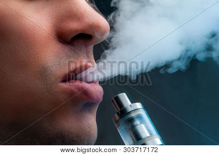 Close-up - Young Man Vaping E-cigarette. New Popular Vaping Device. Vapour, Vaping Concept