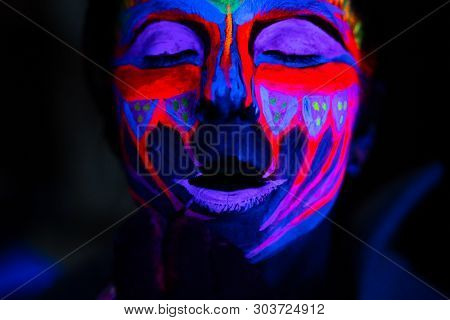Ultraviolet Black Light Glowing Bodyart Processing On Young Womans Face. Pink And Purple Dyes In Col