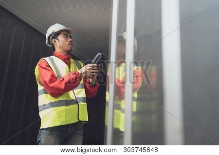 Asian Man Reefer Technician Is Seriously Working And Monitoring Reefer Container At The Port. Engine