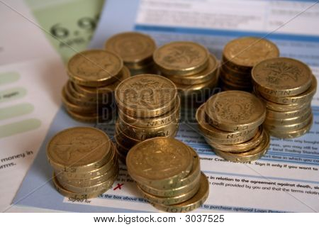 Stacks Of Uk Pound Coins Resting On Loan Application Form