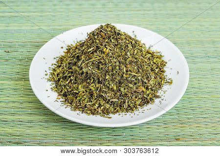 A Heap Of Dry Tarragon Or Estragon Flakes On A White Saucer On A Green Table Mat Made Of Natural Pla