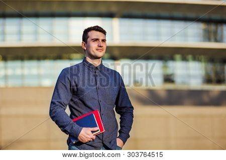 University. Smiling Young Student Man Holding Books Looking To The Side On A University Background .