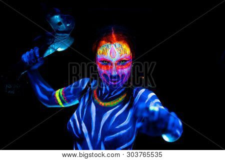 Portrait Of Young Naked Bodyarted Woman In Blue Glowing Ultraviolet Paint With Tomahawk Ancient Preh