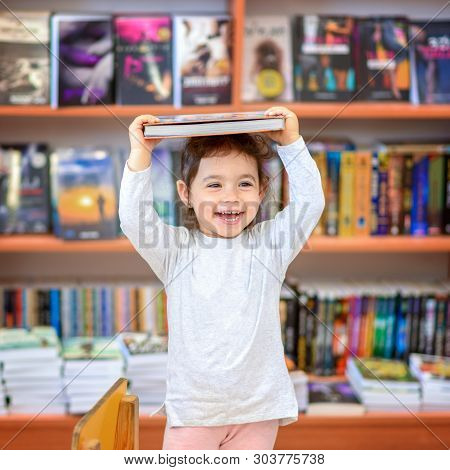 Cute Young Toddler Standing And Holding Book In Head. Little Happy Laughing Girl Indoors In Front Of