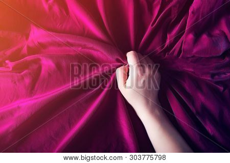 Woman hand on the silk bedding, sex and orgasm concept poster