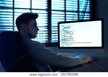 Man Using Computer In Dark Room. Criminal Offence