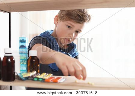 Little child taking pills from shelf at home. Danger of medicament intoxication poster