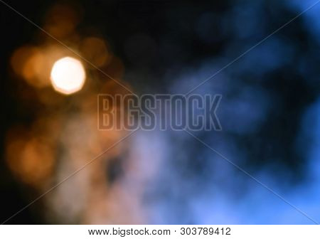 Blurred Bokeh Sunset With Orange And Sky Blue Colours  With Tree Branches Intentionally Blurred To C