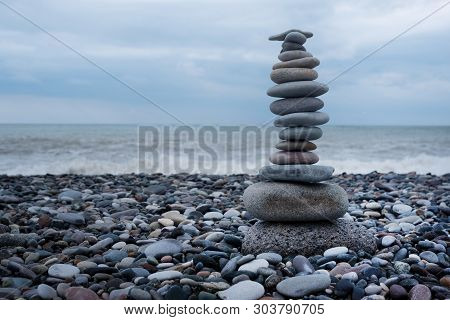 Relaxation At Sea. Stack Of Stones On Beach - Nature Background. Stone Cairn On Green Blurry Backgro
