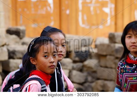 Young Girls In A Village Near The Rice Fields Of Yunnan, China. The Famous Terraced Rice Fields Of Y
