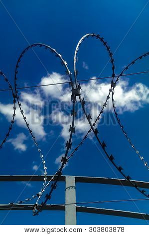 Closeup view of barbed wire fence forming a shape of heart on blue cloudy sky background. Soul barbed wire. Symbol danger warning. Frame of war and peace. Minimalist strange concept. poster