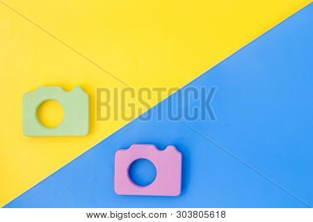 Photo Camera Concept On Yellow And Blue Background Top View Mock Up
