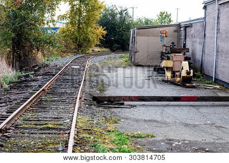 Old Mechanic Garage Building With Equipment And Railroad Tracks In Daylight