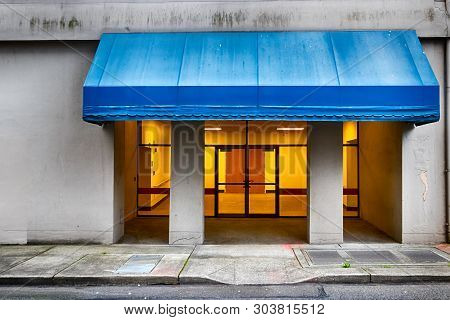 City Building Entrance With Blue Awning And Yellow Light From Inside