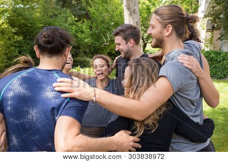 Group Of Happy People Embracing Each Other After Workout. Men And Women In Fitness Apparels Forming