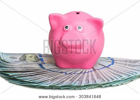 Pink Piggy Bank Standing On A Fan Of A Pile Of American Dollars On A White Background Isolated