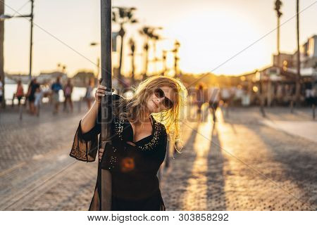 Pretty tourist girl with blond hair in black swimsuit and pareo walking on the bay near sea poster