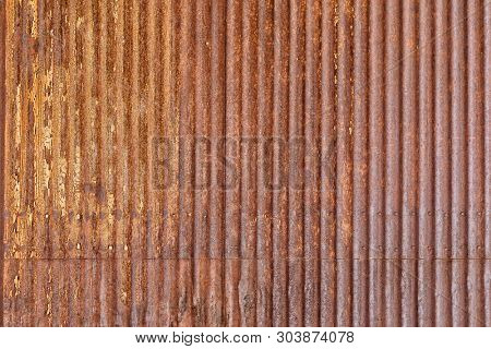 Rusty sheet of corrugated metal wall, as a textured background