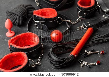 Set of erotic toys for BDSM. The game of sexual slavery with handcuffs, whip, gag and leather straps. Intimate games poster