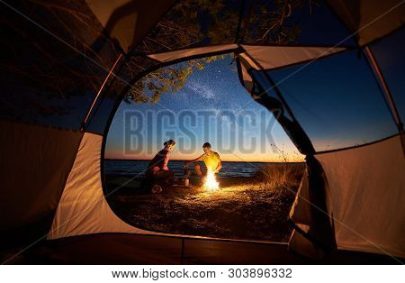 Camping On Sea Shore At Sunset, View From Inside Tourist Tent. Young Couple Hikers, Man And Woman Pr