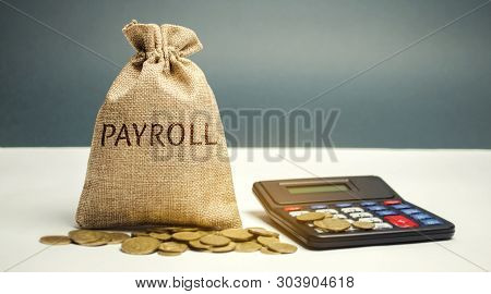 Money Bag With The Word Payroll And Calculator. Payroll Is The Sum Total Of All Compensation A Busin