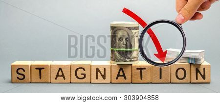 Wooden Blocks With The Word Stagnation And Dollars. Prolonged Period Of Slow Economic Growth, Measur