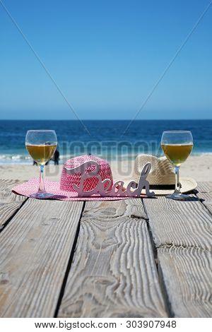 Beach Vacation. White Wine. Sun Hat. Beach scene. Summer accessories. Summer concept.