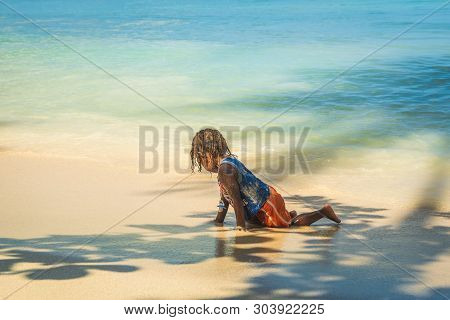 Young Kid Playing On Tropical Beach. Young Kid Relaxing In Vacation. Kid Playing On Tropical Beach I