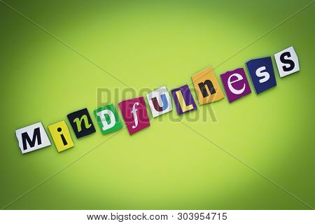 Word Mindfulness From Cut Letters On Green Background. Psychologic Concept. Headline - Mindfulness.