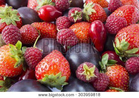 Various Fresh Summer Fruits. Ripe Strawberries, Raspberries, Red Berries And Plums. Texture Fruits C