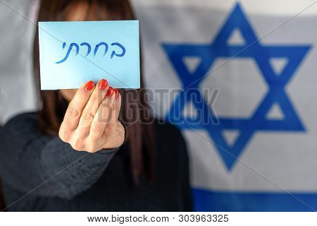 Young Woman Holding Ballot Front Of Face On Israeli Flag Background.hebrew Text I Voted On Voting Pa