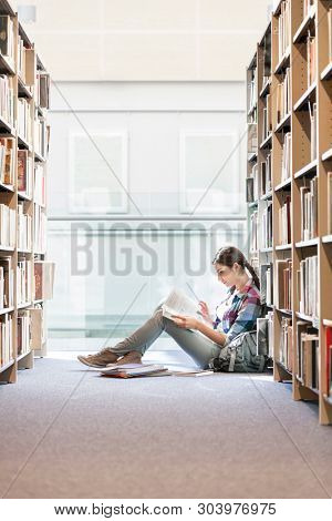 Teenager reading book while sitting against bookshelf at library