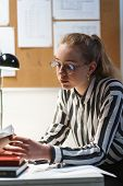 Photo of brooding caucasian woman architect wearing glasses sitting at workplace with house model in office poster