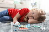 Little child with many different pills on floor at home. Danger of medicament intoxication poster