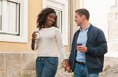 Happy cheerful interracial couple enjoying date. Afro American girl and her Caucasian boyfriend holding hands, walking around old city and enjoying coffee break. Love and leisure concept poster