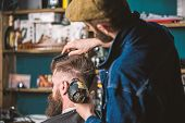 Hipster bearded client getting hairstyle. Barber with hairdryer drying and styling hair of client. Barber with hairdryer works on hairstyle for bearded man, barbershop background. Styling concept poster