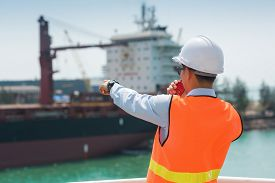Foreman Using Walkie-talkie And Safety Helmet To Work In Cargo Ship