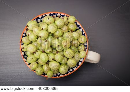 Fresh Gooseberries In Glass Bowl On Black Stone Slate Background. Top View.