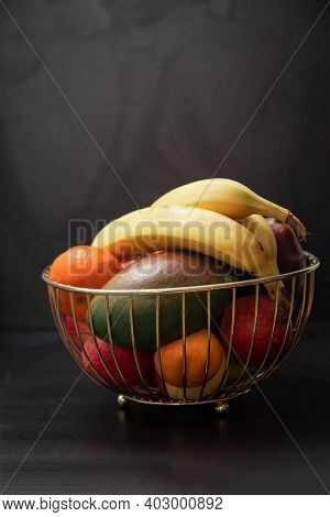 Tasty Fruits In A Metal Basket. Wire Basket With Fruits On Black Background. Healthy Eating Concept