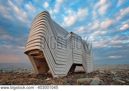 Beach Chaise Lounges Stacked In A Row On The Shore With Beautiful Cloudy Blue Sky Background
